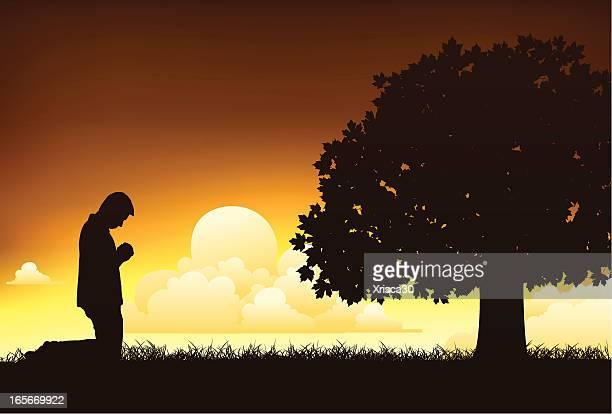 Young man on his knees praying