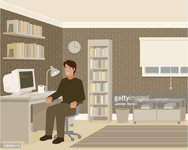 Young Man Sitting at Computer Desk in Home Office