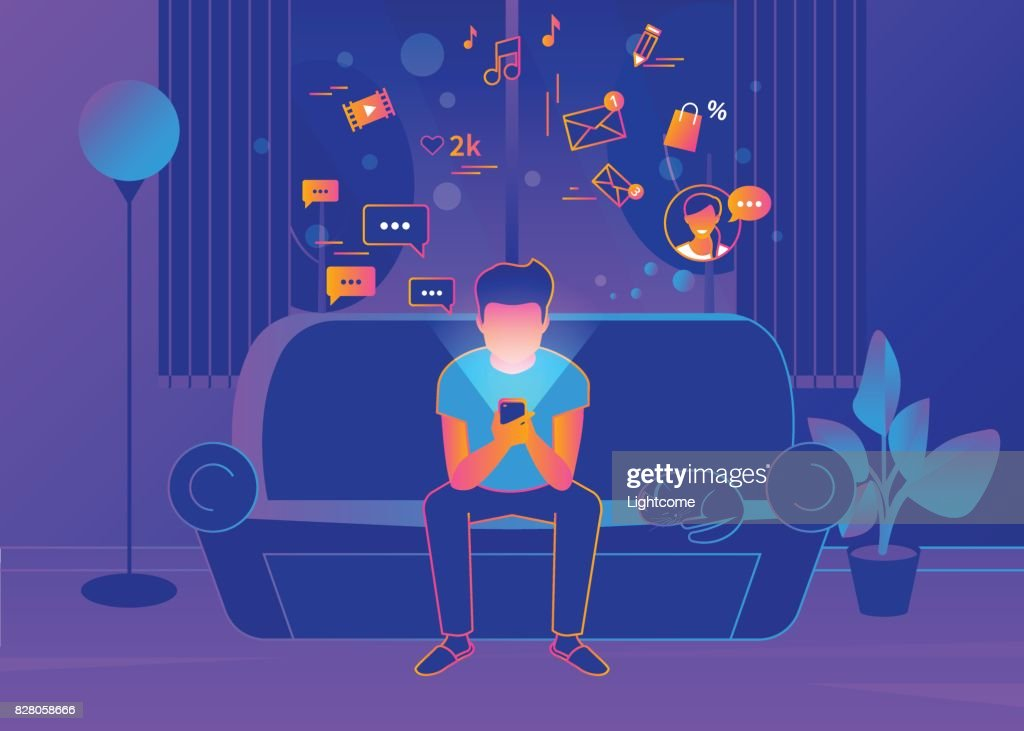 Young man sitting at home on the couch and texting messages