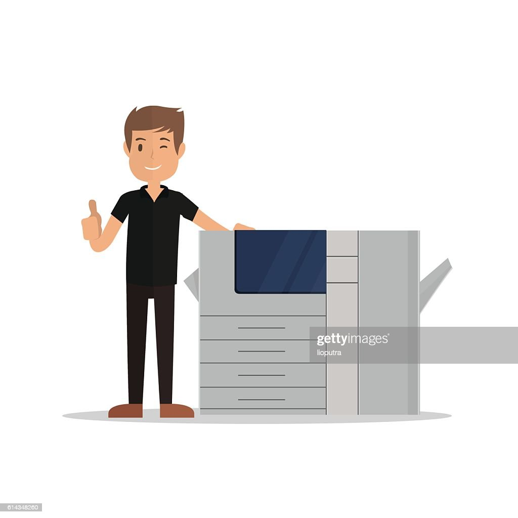 young man standing near printer and pointing thumbs up