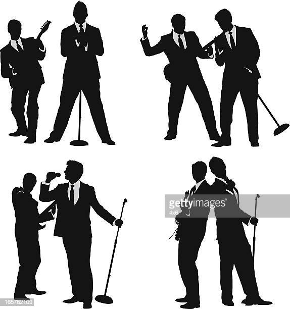 Young men in suits singing and playing guitar