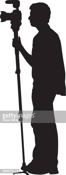 young photographer holding monopod with camera - camera stand stock illustrations, clip art, cartoons, & icons