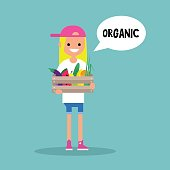 Young vegetarian blond girl holding a crate
