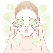 Young woman applying facial mask and sliced cucumbers