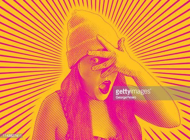 Young woman peeking through fingers