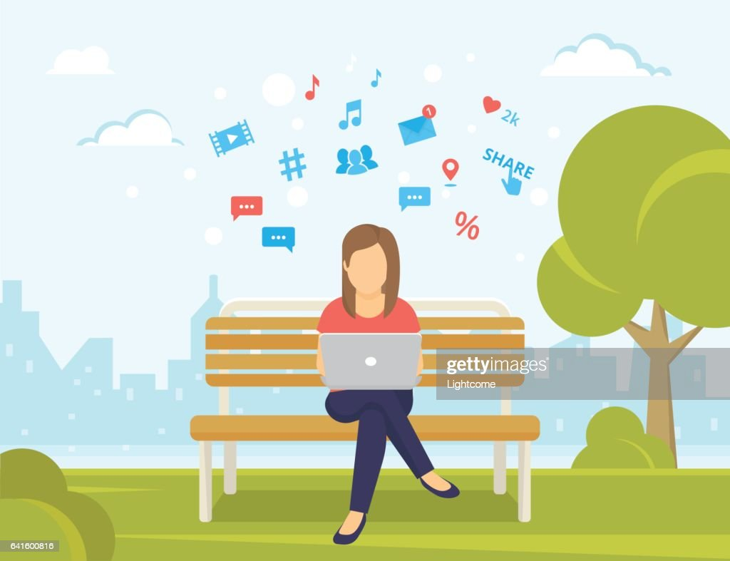 Young woman sitting in the park on the bench and working with laptop
