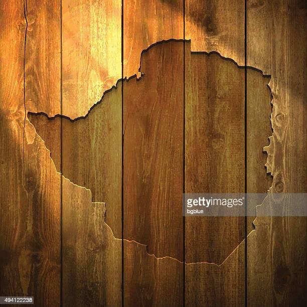 zimbabwe map on lit wooden background - zimbabwe stock illustrations, clip art, cartoons, & icons