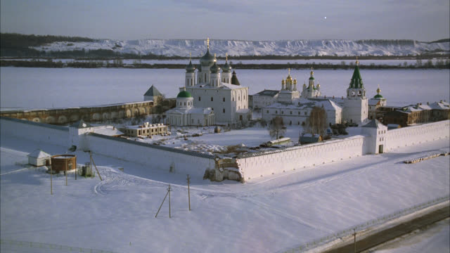 aerial of makariev monastery near nizhny novgorod on the frozen volga river. could be fortress, castle, convent, russian orthodox church or cathedral with onion domes. snow. walls with guard towers, turrets. russian countryside or rural area. - convent stock videos & royalty-free footage