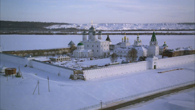 aerial of makariev monastery near nizhny novgorod on the frozen volga river. could be fortress, castle, convent, russian orthodox church or cathedral with onion domes. snow. walls with guard towers, turrets. russian countryside or rural area. - 女子修道院点の映像素材/bロール