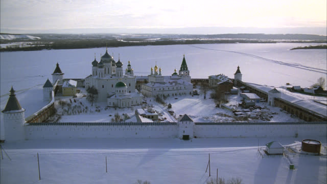 aerial of makariev monastery near nizhny novgorod on the frozen volga river. could be fortress, castle, convent, russian orthodox church or cathedral. snow. walls with guard towers, turrets. onion domes. russian countryside or rural area. - convent stock videos & royalty-free footage