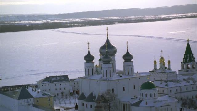 aerial of onion domes on makariev monastery near nizhny novgorod on the frozen volga river. could be fortress, castle, convent, russian orthodox church or cathedral. snow. walls with guard towers, turrets. russian countryside or rural area. - convent stock videos & royalty-free footage