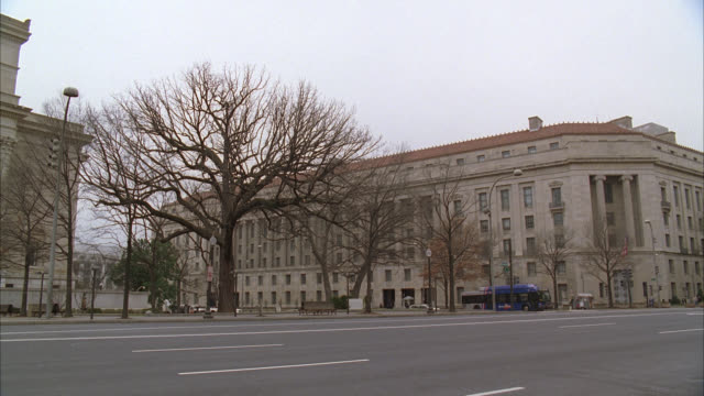 stockvideo's en b-roll-footage met pan right to left of black suv driving on city street with other cars. national archives building or museum. bare branches on trees. could be government office buildings in bg. - national archives washington dc