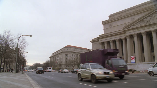 stockvideo's en b-roll-footage met pan left to right of black suv driving on city street with other cars. national archives building or museum. bare branches on trees. could be government office buildings in bg. - national archives washington dc