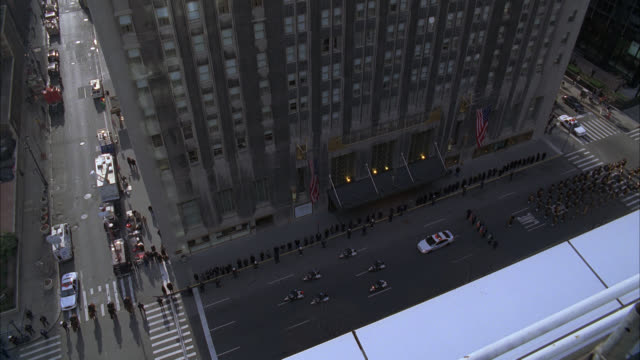 high angle down of waldorf astoria, upper class, hotel entrance in new york as funeral procession on city street. park avenue. could be police officer funeral. - ウォルドルフ・アストリア点の映像素材/bロール