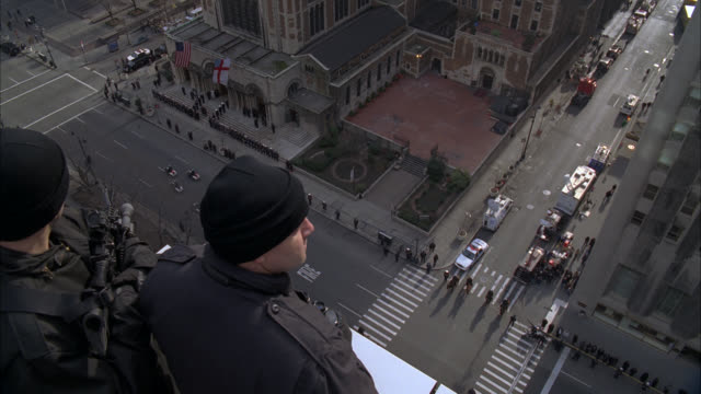 high angle down of waldorf astoria hotel entrance in new york as funeral procession moves by on city street. could be police officer funeral. snipers or secret service officers on rooftop with binoculars and rifles. - ウォルドルフ・アストリア点の映像素材/bロール
