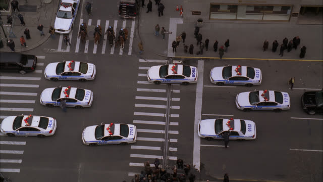 high angle down of police cars in city street, park avenue. people in black stand on sidewalk. could be funeral procession. police officers on horseback. - funeral procession stock videos & royalty-free footage