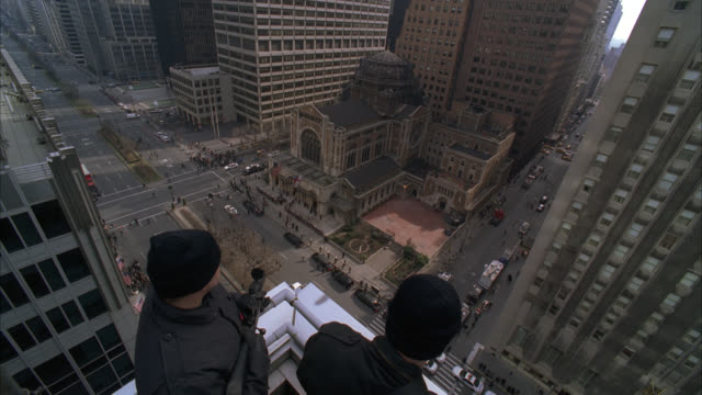 high angle down of snipers or secret service agents with guns, weapons or rifles on rooftop of high rise office or apartment building in midtown manhattan. st. bartholomew's episcopal church. domed brick building. funeral procession. police cars on city s - waldorf astoria stock videos & royalty-free footage