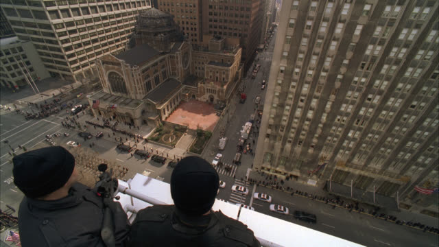 high angle down of snipers or secret service agents with guns, weapons or rifles on rooftop of high rise office or apartment building in midtown manhattan. st. bartholomew's episcopal church. domed brick building. funeral procession. police cars on city s - ウォルドルフ・アストリア点の映像素材/bロール