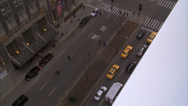 HIGH ANGLE DOWN OF ENTRANCE TO WALDORF ASTORIA HOTEL ON PARK AVENUE. UPPER CLASS. AWNING OVER ENTRANCE. TAXIS, CARS, AND LIMOS VISIBLE. PEDESTRIANS. NEW YORK.