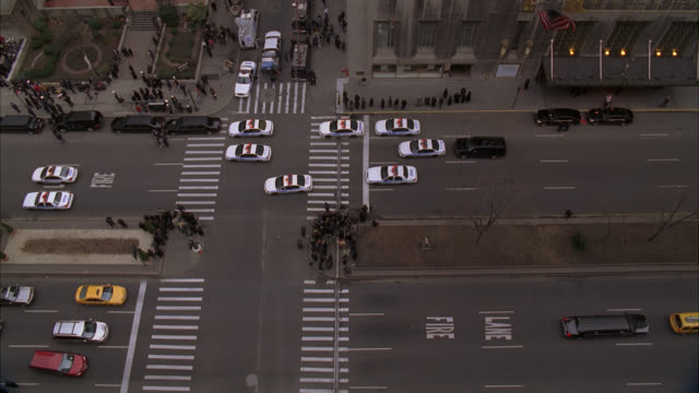 high angle down of entrance to waldorf astoria hotel on park avenue. upper class. awning over entrance. taxis and cars visible on city street. police cars in formation on street. could be for funeral procession or parade. - ウォルドルフ・アストリア点の映像素材/bロール