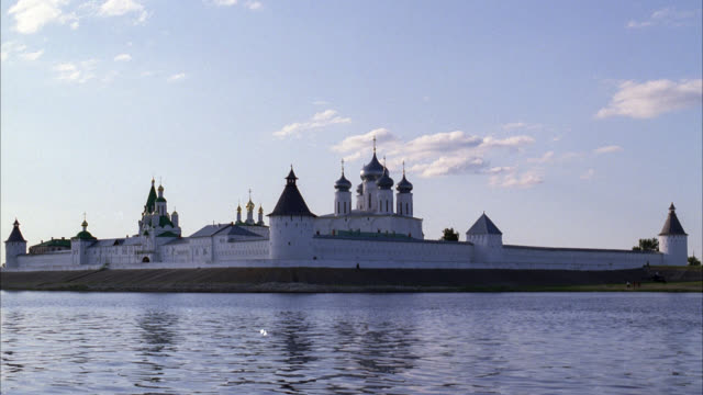 WIDE ANGLE OF MAKARIEV MONASTERY ALONG THE VOLGA RIVER NEAR NIZHNY NOVGOROD. GUARD TOWERS IN WALLS AND BUILDINGS WITH ONION DOMES. COULD BE A CASTLE, CONVENT, CHURCH, CATHEDRAL OR FORT. SUN REFLECTING OFF WATER.