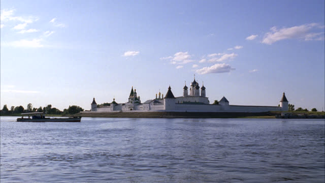 WIDE ANGLE OF FERRY OR BOAT TAXI MOVING PAST MAKARIEV MONASTERY ALONG THE VOLGA RIVER NEAR NIZHNY NOVGOROD. GUARD TOWERS IN WALLS AND BUILDINGS WITH ONION DOMES. COULD BE A CASTLE, CONVENT, CHURCH, CATHEDRAL OR FORT.