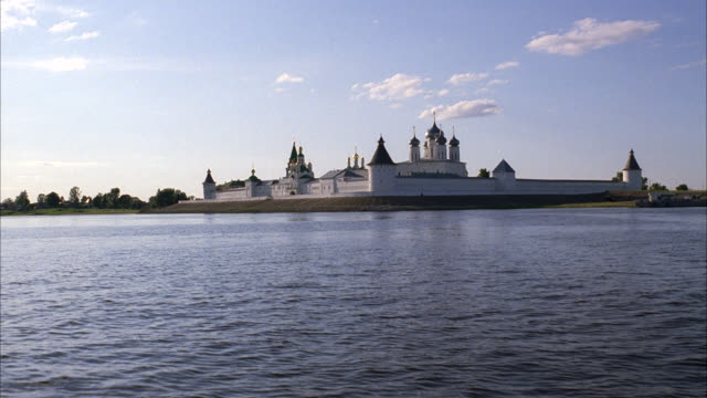 WIDE ANGLE OF MAKARIEV MONASTERY ALONG THE VOLGA RIVER NEAR NIZHNY NOVGOROD. GUARD TOWERS IN WALLS AND BUILDINGS WITH ONION DOMES. COULD BE A CASTLE, CONVENT, CHURCH, CATHEDRAL OR FORT.