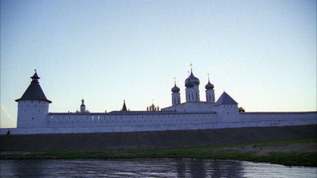 pan down from sky to makariev monastery near nizhny novgorod on volga river. buildings surrounded by walls with guard towers. buildings have towers, onion domes. could be fortress, castle, convent, russian orthodox church or cathedral. river banks. - convent stock videos & royalty-free footage