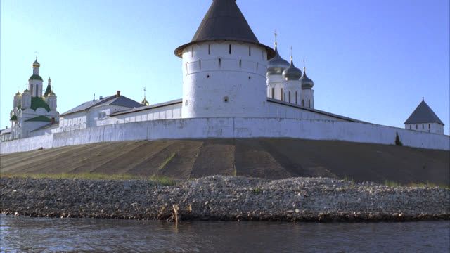 medium angle of makariev monastery near nizhny novgorod on the volga river. could be fortress, castle, convent, russian orthodox church or cathedral. walls with guard towers, turrets. onion domes. - 女子修道院点の映像素材/bロール