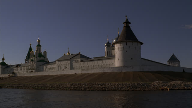 wide angle of makariev monastery near nizhny novgorod on volga river. buildings surrounded by walls with guard towers. buildings have towers, onion domes. people walking up steps on rocky river bank toward monastery. could be fortress, castle, convent, ru - convent stock videos & royalty-free footage