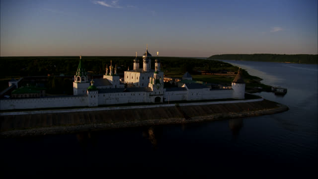 aerial over makariev monastery near nizhny novgorod on the volga river surrounded by rural area or countryside. could be fortress, castle, convent, russian orthodox church or cathedral. walls with guard towers, turrets. buildings with onion domes. woman w - convent stock videos & royalty-free footage