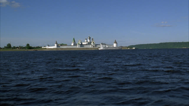 wide angle of makariev monastery near nizhny novgorod on the volga river. could be fortress, castle, convent, russian orthodox church or cathedral. walls with guard towers, turrets. buildings with onion domes. countryside or rural area in bg. small boat o - convent stock videos & royalty-free footage