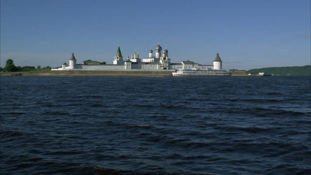pan up from water to makariev monastery near nizhny novgorod on the volga river. could be fortress, castle, convent, russian orthodox church or cathedral. walls with guard towers, turrets. buildings with onion domes. countryside or rural area in bg. small - convent stock videos & royalty-free footage