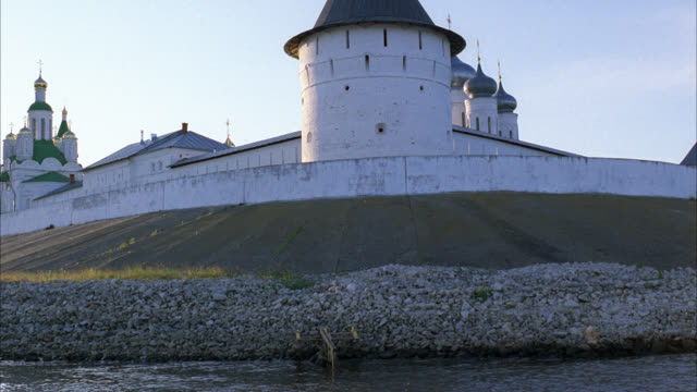 MEDIUM ANGLE OF MAKARIEV MONASTERY NEAR NIZHNY NOVGOROD ON THE VOLGA RIVER. COULD BE FORTRESS, CASTLE, CONVENT, RUSSIAN ORTHODOX CHURCH OR CATHEDRAL. WALLS WITH GUARD TOWERS, TURRETS. BUILDINGS WITH ONION DOMES.