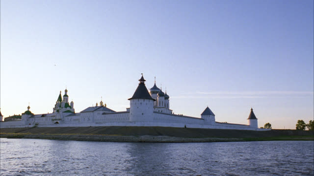 wide angle of makariev monastery near nizhny novgorod on the volga river with countryside or rural area in bg. could be fortress, castle, convent, russian orthodox church or cathedral. walls with guard towers, turrets. buildings with onion domes. - 女子修道院点の映像素材/bロール
