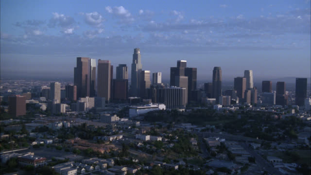 aerial zoom in on downtown los angeles city skyline. skyscrapers and high rise office or apartment buildings. houses and multi-story apartment buildings in residential areas. - 1998 stock-videos und b-roll-filmmaterial