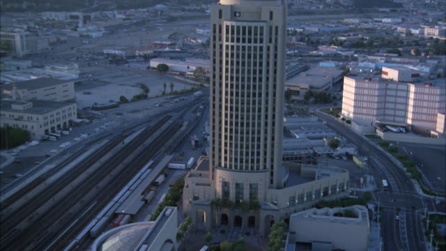 vidéos et rushes de aerial of high rise metropolitan transportation office building at union station, train station. downtown los angeles city. railroad tracks and multi-story apartment buildings in bg. urban area. - union station los angeles