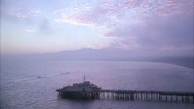 AERIAL OF SANTA MONICA PIER, BOARDWALK OR AMUSEMENT PARK. FERRIS WHEEL AND ROLLER COASTER. BEACH, OCEAN WAVES. LOS ANGELES AREA.