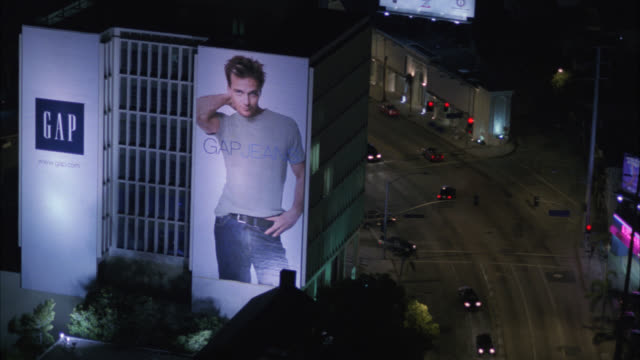 aerial of sunset boulevard, sunset strip. cars driving on city streets. billboards and advertisements. west hollywood. high rise office buildings and hotels. bars and nightclubs. - sunset boulevard stock-videos und b-roll-filmmaterial