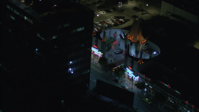 aerial of grauman's chinese theater and el capitan theater on hollywood blvd. movie theaters. bank of hollywood. landmarks. multi-story office and apartment buildings in city of hollywood. neon lights and signs. - tlc chinese theater bildbanksvideor och videomaterial från bakom kulisserna
