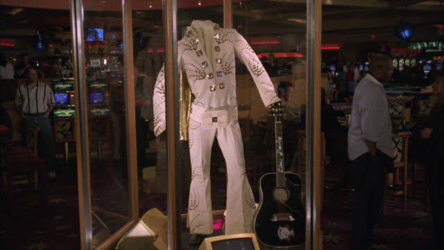 medium angle of elvis exhibit with white suit and guitar on display in glass case. costumes or clothing. people at slot machines and games in bg. bar in bg. gambling, hard rock hotel and casino. las vegas. - ハードロックカフェ点の映像素材/bロール