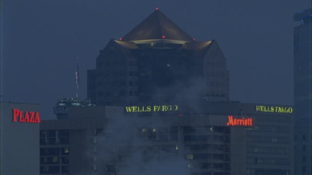 MEDIUM ANGLE OF TOPS OF PLAZA, MARRIOT HOTEL, WELLS FARGO BUILDING AND ONE UTAH CENTER SKYSCRAPER. STEAM RISES FROM UNSEEN SOURCE IN FRONT OF HIGH RISE BUILDINGS. AMERICAN FLAG SEEN ATOP BUILDING.