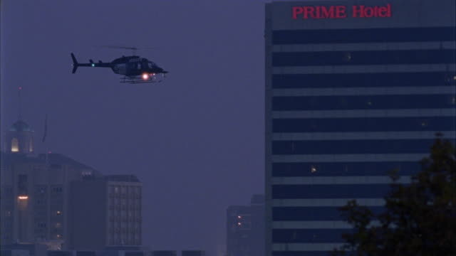PAN LEFT TO RIGHT FOLLOWS HELICOPTER DESCENDING PAST PRIME HOTEL BUILDING AS IF TO LAND AMONG TREES IN DOWNTOWN SALT LAKE CITY. PANS LEFT TO SHOW DOWNTOWN THEN SALT LAKE LDS TEMPLE. COPTER COULD BE POLICE VEHICLE.