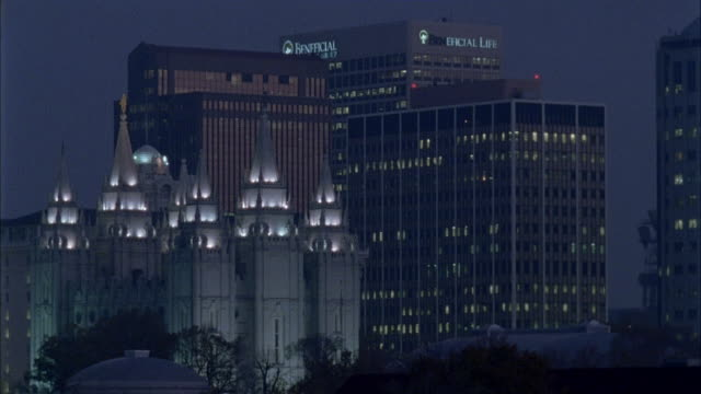 WIDE ANGLE OF SALT LAKE LDS TEMPLE AMONG DOWNTOWN SKYSCRAPERS AND HIGH RISES. CHURCH IS LIT UP.