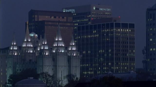 vídeos de stock, filmes e b-roll de wide angle of salt lake lds temple among downtown skyscrapers and high rises. church is lit up. - salt lake city utah