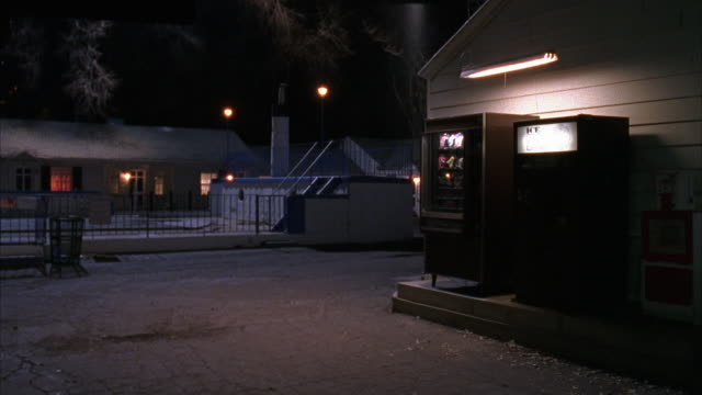 STEADICAM MOVES ALONG MOTEL DRIVEWAY PAST VENDING MACHINES, COVERED SWIMMING POOL AND OFFICE AROUND CORNER SHOWING PARKED SUV AND CABIN LIKE MOTEL ROOMS. OBJECT PARTIALLY OBSCURES FRAME IN PORTION OF CLIP.