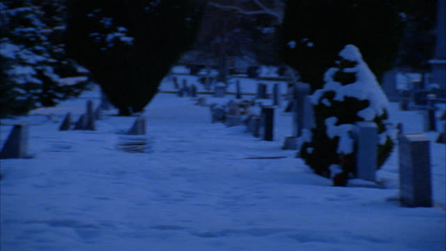 PAN RIGHT TO LEFT AND BACK REPEATEDLY SHOWS SNOW COVERED CEMETERY WITH  TOMBSTONES, HEADSTONES, GRAVESTONES. COULD BE POV OF PERSON LOOKING AROUND GRAVEYARD.