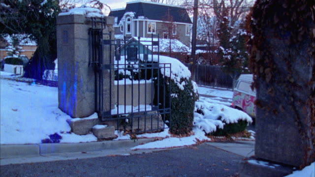 PAN RIGHT TO LEFT SHOWS GATES TO CEMETERY AS COLORFUL HIPPIE VOLKSWAGEN BUS DRIVES THROUGH ONTO GRAVEYARD DRIVEWAY. SNOW COVERS GRAVES.