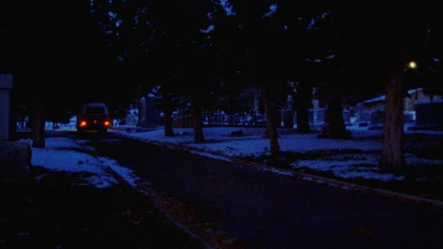 WIDE ANGLE OF COLORFUL HIPPIE VOLKSWAGEN BUS DRIVING AWAY THROUGH  GRAVEYARD. SNOW COVERS CEMETERY'S GRAVES. VANS.