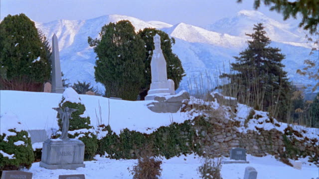 WIDE ANGLE OF TOMBSTONES ON HILL IN SNOW COVERED CEMETERY. GRAVEYARD HAS HEADSTONES, GRAVESTONES. MOUNTAIN RANGE SEEN IN BACKGROUND. COULD PASS FOR EUROPE.
